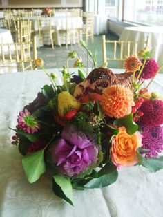 Thanksgiving centerpiece for wedding with cornucopia on a bed of autumn flowers with fruit by Limelight Floral Design Hoboken NJ