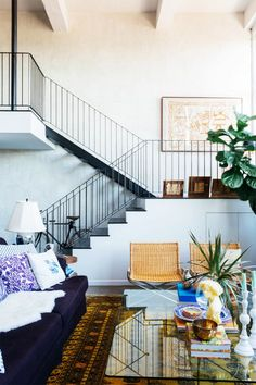 Living room with high ceilings, a large yellow Persian area rug,  and a purple sofa