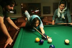 Upper-class youth visit Kish Island for leisure and fun. In Tehran, Islamic law prohibits women to play billiards. Iran - April 2006. by  Alfred Yaghobzadeh