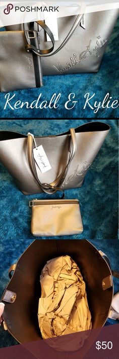 "KENDALL & KYLIE SHIMMERY GRAY TOTE W/ WRISTLET! Shimmery gray tote with Kendall and Kylie embossed on the side. It has 2 handles and a silver magnetic snap closure. The inside is one open compartment.  It also comes with a matching wristlet that you can attach to the handles!!    DIMENSIONS: TOTE is Approximately 20""L x 12""H x 8""W  WRISTLET is Approximately 10""L x 7""H x 1""W  BRAND-NEW WITH TAGS!! Kendall & Kylie Bags"