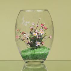 Showcase a small flower arrangement inside a large glass vase. Glass chips in the bottom pull the look together.