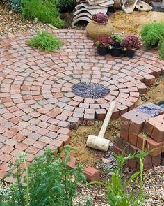 Building a patio with brick pavers in garden construction .LOVE the circle/round visual of this patio.