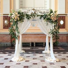 Vintage 1920's inspired chuppah covered in east texas smilax with creme de la creme roses, polo roses, jana spray roses, tardiva hydrangea, and draped with sheer fabric by Sebesta Design
