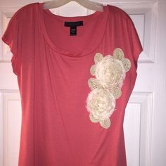 Ashley Stewart Blouse Salmon / Coral colored this fabric blouse with super cute cream flower patches. They probably need to be re-glued or fabric taped to secure them better. LongEr length than a regular t-shirt. Perfect spring top to dress up or rock with jeans! Ashley Stewart Tops Tees - Short Sleeve