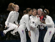 Susie Scanlan (L), Kelley Hurley (2nd L), Courtney Hurley (C) and Maya Lawrence of the U.S. (R) celebrate their victory with their coach at the end of the women's eppe team bronze medal fencing competition against Russia at the ExCel venue during the London 2012 Olympic Games August 4, 2012. REUTERS/Damir Sagolj (BRITAIN - Tags: OLYMPICS SPORT FENCING TPX IMAGES OF THE DAY)