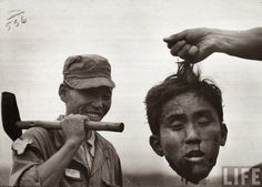 "From the archives of LIFE Magazine ... ""A member of the South Korean National Police holds the severed head of a North Korean communist guerilla during the Korean War, 1952."" /From The Cab: Man's Inhumanity - 4"