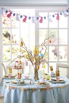 What a fun table setting...love the whimsical centerpiece and the bunny bunting with the little pom pom tails are so cute!