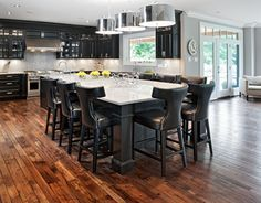 Like any tuxedo, which is best matched with a bow tie, this kitchen is complimented with a center island and attached marble table with colonial posts. The island has a terrific bar sink and a custom door frame wine fridge that makes it easier to entertain.