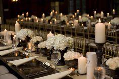 Alternanza di ortensie bianche, rose e candele tutto rigorosamente total white. Un accostamento ben studiato con le sedie oro le tonalità molto scure del resto dell'allestimento
