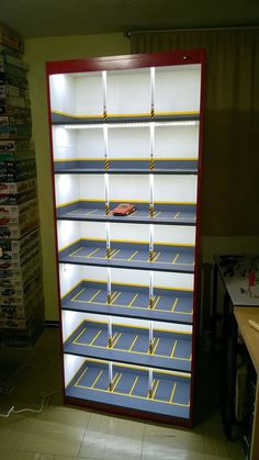 Creative model car display cabinet looks like lighted parking garage.