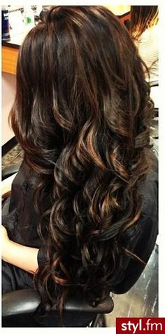 Gorgeous subtle highlights and lowlights on dark, curled hair.