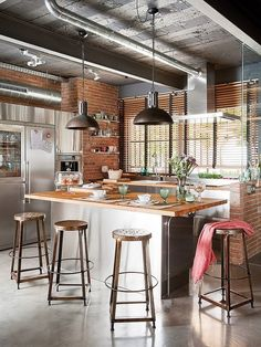 Contemporary Kitchen with Pendant Light, Stainless Steel, John Boos & Co. Blended Maple Countertop, L-shaped, Kitchen island    industrial vibe. wrap around seating at island. exposed bricks. lighting...
