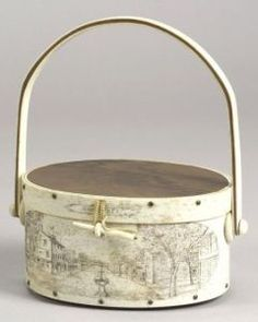 """Engraved Whale Bone and Rosewood Nantucket Ditty Box Handbag, Sconset Scrimshaw, Long Island, New York, 1971, oval covered box with curved sides secured with five fingers, hinged lid with rosewood top and bottom, swing handle, embellished on the sides with scenes of Nantucket including a village, a lighthouse, and a windmill, the interior lined with brown suede, signed """"J.J. Cochran"""" on the back, ht. 4, dia. 8 3/8 in"""