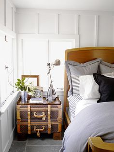 Nothing zaps that stark feel faster than weathered antiques. This inviting bedroom uses old suitcases as a nightstand.