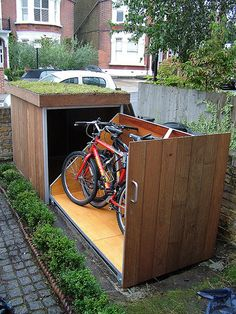 Slide-out, metal bike locker with wood siding and rooftop garden.