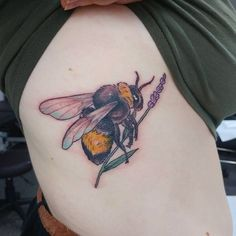 This Colorful Rib Piece. Bee is a symbol of vulnerability due to its non-violent nature and this tattoo express this trait of the wearer too.