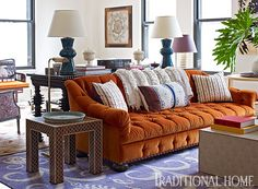 A tufted sofa in the living room is upholstered in a burnt orange color. - Photo: Francesco Lagnese / Design: Anne Maxwell Foster and Suysel dePedro Cunningham