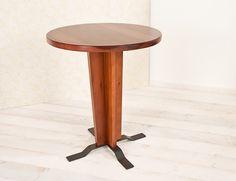 Table 100. Solid toulipier table with a central base, metal feet and round surface. Tavolo 100. Tavolo in toulipier massello, base centrale con piedini in metallo e piano tondo.