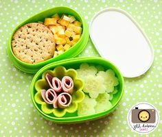 Lots of cute kids' lunch ideas,mostly in bento boxes, like this one with cubed cheese, whole grain crackers, lunchmeat rolls (in silicon muffin mold), and flower-cut cucumbers.