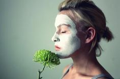 Young woman with face mask and flower - -Rekha Garton-/Moment/Getty Images