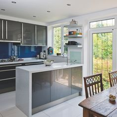 Grey marble kitchen - interesting addition of rustic wooden table and metal? floating shelving, without which this kitchen might not be inviting ... the windows and door add much appeal.