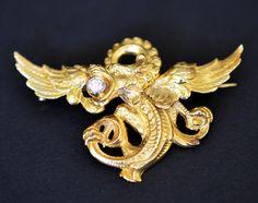 uperb late Victorian era convertible necklace pendant / diamond brooch with a typical Griffon / Griffin or also called Gryphon design. The pendant / brooch depicts an open winged flying griffin with a sparkling round brilliant cut diamond in its mouth.