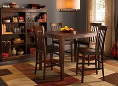 Less is more with the 52nd Street 5-piece counter-height dining set. Crafted with simple lines and covered from top to bottom with a rich cherry finish, the set's beautiful wood speaks for itself. Slightly tapered legs and back slats keep with the streamlined design and add timeless appeal.