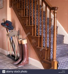 Leather riding boots at the foot of staircase with blue patterned carpet Stock Photo