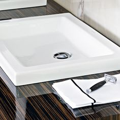 Fine veneer and high-gloss varnish add a hint of luxury to the white wash basin.