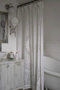 A old lace tablecloth for a shower curtain... a bowl sink and a vintage cabinet ..... Linprobable coup de Coeur