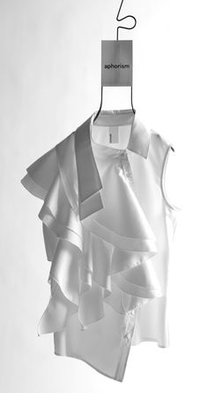 White shirt reinvented with an asymmetric cut, cascading ruffles & disjointed collar - fashion design details; fashion construction //