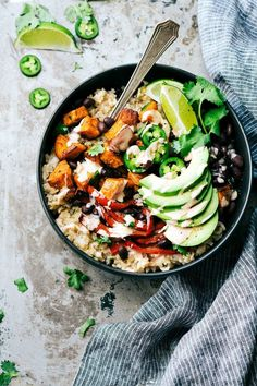 A delicious and simple to make veggie burrito bowl -- brown rice, seasoned & roasted sweet potatoes + bell peppers, black beans, and avocado