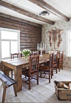 Ruokahuoneen jykevä pöytä on itse tehty, seuraksi sille on hankittu tuolit Maskusta. K-raudan tapetti luo hyvän kontrastin tummalle hirsiseinälle. Porontalja on matkamuisto Kittilästä ja kynttilänjalka Juvan Puutarhasomisteesta. Talosta löytyneessä puulaatikossa säilytetään halkoja. Cabin Homes, Log Homes, Knotty Pine Walls, Oregon House, Simply Home, Pole Barn Homes, Cottage Interiors, Wooden House, House In The Woods