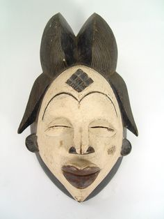 West African Punu Mask. Traditionally, Punu masks represent idealized female ancestors' faces. The classic Punu mask styling includes an eleborate hairdo (popular among the Punu women), realistic, usually white faces with full lips, high-domed foreheads, high eyebrows, and diamond-shape scarification marks on the foreheads and temples. The elaborate Punu hairstyles suggest that the wearer is wealthy as her hair has not been flattened by the need to carry goods.   $190.00
