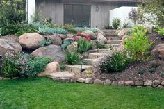 Stone staircase to lawn with large bolder landscape
