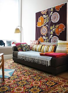 I LOVE the wall hanging, the rug, the pillows. Do not like the striped blanket on the sofa, nor the style of the sofa. But what a great combination of colors!