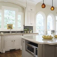 Arched Windows  The low-high-low profile of this kitchen window fits neatly into the arch above it, adding a dimension of interest. This choice also reflects the series of arched windows in the dining room. Using different but complementary window styles in each room helps define the connected spaces.