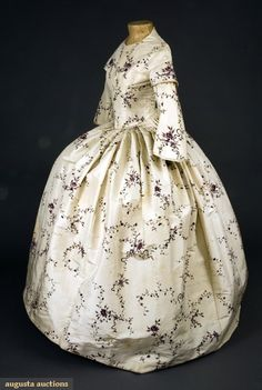 PAINTED CREAM SILK GOWN, ENGLAND, c. 1850-Cream silk ribbed taffeta hand painted with delicate floral vine, long boned bodice with rounded dip in piped waistline, high round neckline, narrow bell sleeves with short shoulder caps, piped seams, full skirt knife-pleated with back gathers, brass hook & eye center back closure, glazed linen bodice lining, stiffened cotton gauze skirt lining, silk hem facing, (scattered brown foxing, large brown stain in skirt, cream satin bias trim missing on...)