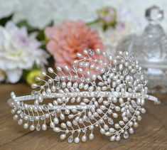 Feather This beautiful headpiece has been crafted out of silver plated wire and is adorned with an array of sparkling Swarovski crystal beads and stones, and a luxurious combination of Swarovski and AA grade freshwater pearls. The band on this piece can be wrapped in the colour of your choice to blend in with your hair, just send a message. All headpieces are wrapped and boxed.