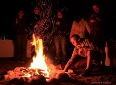 Guests compare photos and share stories of a Leopard sighting while standing around the campfire.