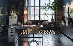 広いホームオフィスの中央にグレーのデスクとバーチとウールカバーのついた会議用チェア。高さの異なるキャビネットが数台。