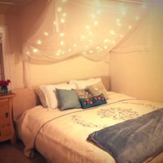 canopy over bed with twinkle lights behind it