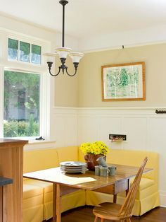 Banquette breakfast nooks maximize space in corner areas. An L-shape bench provides seating on two sides of the table. Extra chairs can be added when needed. The bright yellow bench and flower centerpiece adds personality to the small space.