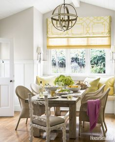Wicker chairs from Janus et Cie surround a custom farm table from Mecox Gardens, accented by cheerful yellow shades and pillows.   - HouseBeautiful.com