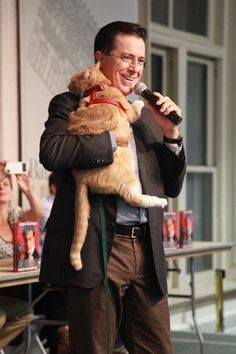 A cat snuggling Stephen Colbert.  All my dreams.