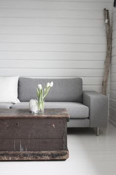 grey contemporary sofa combined with a rustic, painted chest and driftwood