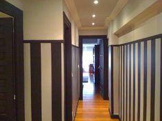 Pasillo empapelado con papel a rayas verticales color negro