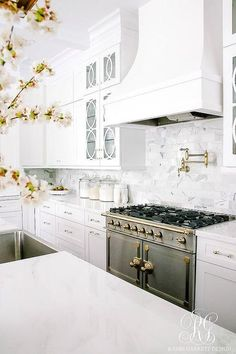 A white marble top island, fitted with a stainless steel apron sink, sits in front of a French stove fixed beneath a polished brass swing arm pot filler mounted to stacked marble backsplash tiles beneath a white French wood hood flanked by stacked seeded glass mullion glass cabinets.