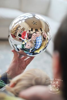 Idea for Christmas Photo Card Pose - reflected in a metallic ornament! I particularly like the kid texting in the background... lol