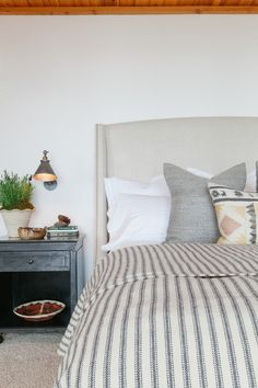 Neutral palette striped bedding upholstered headboard